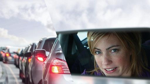 Stau im Berufsverkehr. Eine Frau schaut in den Rückspiegel ihres Wagens.