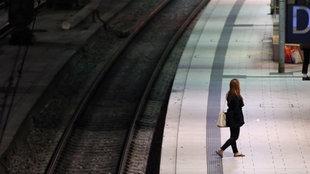 Eine Frau steht am Morgen während des Streiks der Lokführer auf dem Bahnsteig