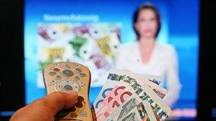 Eine Frau hält eine Fernbedienung und Geldscheine vor einen Fernseher