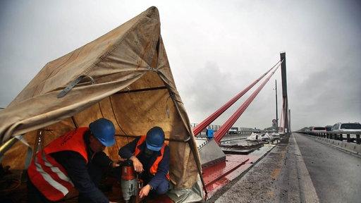 Arbeiter reparieren uf der maroden Rheinbrücke der Autobahn A1 die Halterungen der Stahlseile