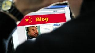 Mann guckt auf Laptop mit chinesischer Flagge und Bild von Ai Weiwei