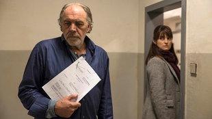 Ein Mann steht nachdenklich in einem Zimmer und hat Unterlagen in der Hand, hinter seinem Rücken schaut ihn eine Frau an die im Türrahmen steht