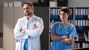 Dr. Moreau und Dr. Koshka mit verschränkten Armen und ernsten Blicken