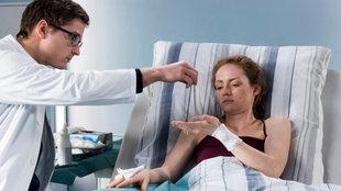 Dr. Elias Bähr überreicht Patientin Rosa eine Kette