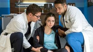 Zwei Ärzte helfen einer jungen Frau auf und beugen sich zu ihr hinunter
