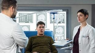 Eine Ärztin zeigt einem Arzt einen Block, zwischen ihnen liegt ein Patient auf einem Krankenbett und schaut den Arzt an
