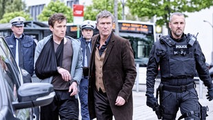 Unter strenger Bewachung (Matthias Schendel) bringt Yves (Philippe Caroit) den potentiellen Kronzeugen Petja Kremer (Artjom Gilz) aus dem Krankenhaus.