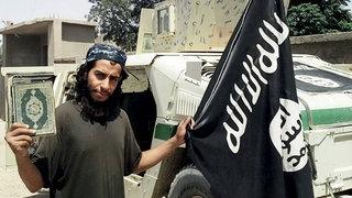 Junger Mann mit Bart hält Koran und Fahne in den Händen
