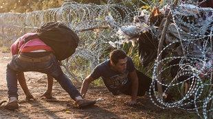 Männer kriechen durch einen Grenzzaun aus Stacheldraht
