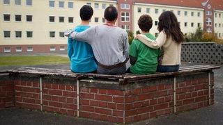 Eine syrische Familie sitzt vor einem Asylwohnheim