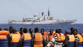 Eine Gruppe von Flüchtlingen auf einem kleinen Boot vor einem Schiff der Marine
