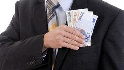 Ein Mann im dunklen Anzug hält mehrere Geldscheine in der Hand