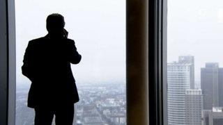 Der Schatten eines Mannes mit Mobiltelefon in einem Büro mit Blick auf Hochhaustürme
