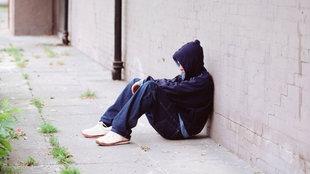 Jugendlicher sitzt an eine Wand gelehnt auf dem Boden