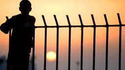 Schattenriss eines Kindes auf einem Grenzzaun