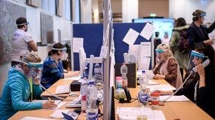 Mitarbeiter*innen telefonieren im Gesundheitsamt Berlin-Mitte.