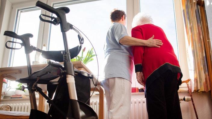 Eine Pflegerin und eine ältere Frau schauen zusammen aus einem Fenster, im Hintergrund ein Rollator