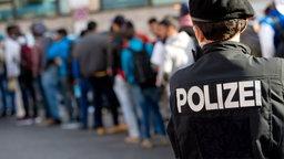 Polizist von hinten mit Schriftzug Polizei auf der Uniformjacke vor eine Schlange mit Flüchtlingen