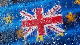 Unionjack vor EU-Flagge hinter regennasser Scheibe