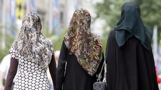 Drei junge Frauen mit Kopftüchern gehen durch die  Innenstadt von München