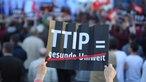 Schild mit Aufschrift TTIP gleich gesunde Umwelt, gesunde Umwelt ist durchgestrichen auf dem Schild