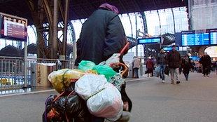 Obdachloser zieht sein Gepäck am Bahnhof hinter sich her
