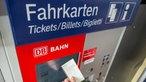Fahrkartenautomat der Deutschen Bahn, die linke Hand einer Person hält die gezogene Fahrkarte