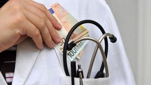 Ein Arzt steckt sich Geldscheine in die Tasche seines Kittels