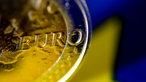 Eine Euromünze vor einem der goldenen Eurosterne der Flagge der EU