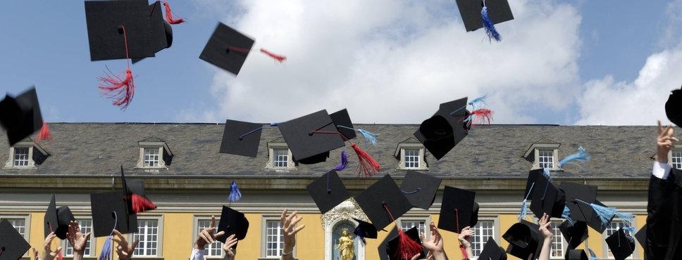 Uni-Absolventen in feierlichen Talar-Gewändern werfen ihre Mützen hoch