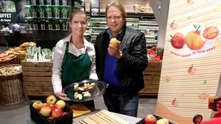 Der Vorkoster Björn Freitag und seine Assistentin Magdalena Stamm präsentieren eine besondere Apfelsorte in einem Kölner Supermarkt.