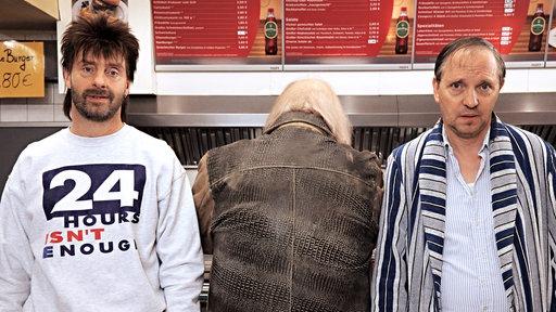 Drei Männer stehen vor einer Imbisstheke