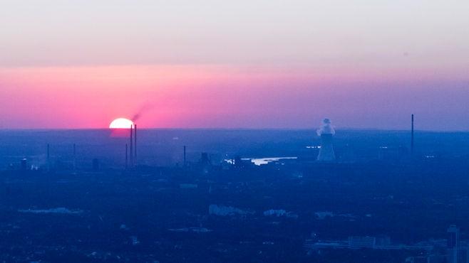Die Sonne geht rot glühend am Horizont unter, im Vordergrund Industrieanlagen.