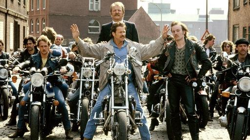 Horst Schimanski auf einer Harley, Kommissar Thanner stehend hinter ihm umgeben von jungen Männer in Lederkluft und Motorrädern.