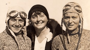 Drei junge Frauen auf einer 20er Jahre Fotografie, davon zwei mit Fliegerhauben