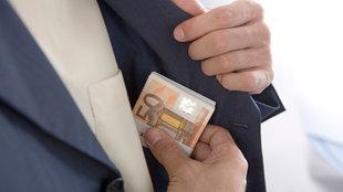Geldscheine werden in eine Jackentasche gesteckt