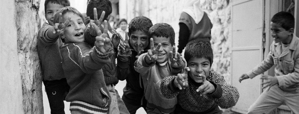 Ein Schwarz-Weiss-Foto, sechs Jungen, um die zehn Jahre alt, posieren selbstbewusst mit dem Victory-Zeichen für die Kamera.