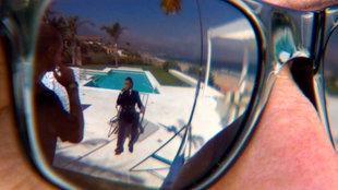 Eine Nahaufnahme einer Sonnenbrille, die von einem Mann getragen wird. In der Sonnenbrille spiegelt sich ein Swimming-Pool und ein Männer-Model auf einem Stuhl.