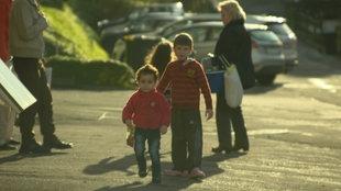 Kinder auf der Straße und eine Frau mit Tasche im Hintergrund
