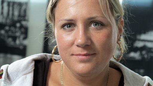 Marion, eine junge Frau, sportlich-lässig gekleidet. Sie hat ein freundliches, rundliches Gesicht und einen zuversichtlichen Blick.