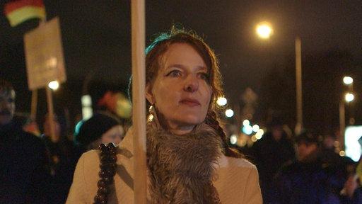 Junge Frau bei einer Demonstration mit Deutscher Fahne im Hintergrund