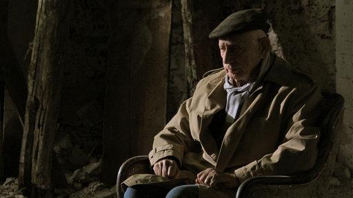 Henryk Schoenker sitzt in den Ruinen seines Elternhauses in Auschwitz