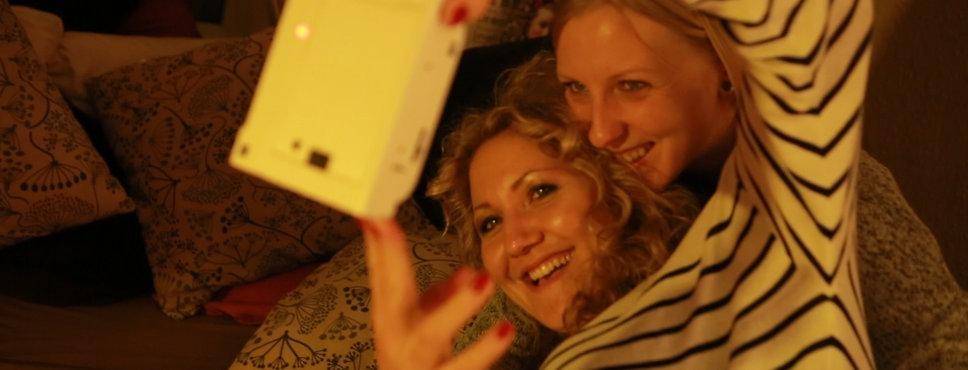 Zwei junge Frauen machen mit einem smartphone Selfies