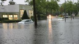 Zwei Autos stehen am 28.07.2014 auf einer überfluteten Straße in Münster.