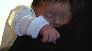 Ein Baby schläft auf dem Arm seiner Mutter