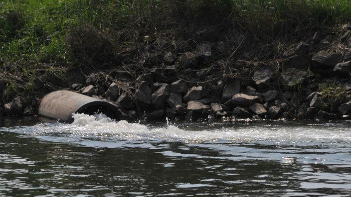 Abwasserrohr leitet Wasser in einen Fluss