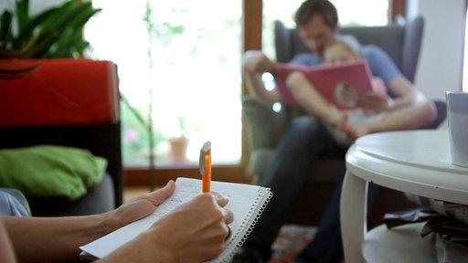 Unscharfes Billd, im Hintergrund sieht man einen Vater, der mit seiner Tochter an Buch anschaut.