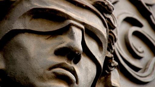 Nahaufnahme einer Justizia-Figur mit verbundenen Augen