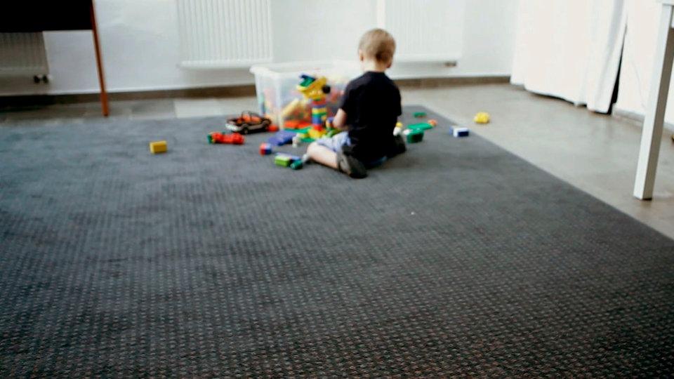 Ein kleines Kind sitzt auf dem Teppich und spielt