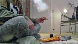 Kiffer sitzt auf dem boden und raucht.